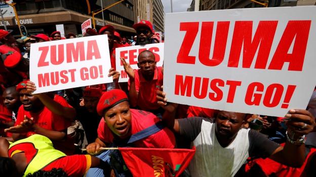 Demonstranten halten ein Plakat, auf dem «Zuma must go» zu lesen ist.