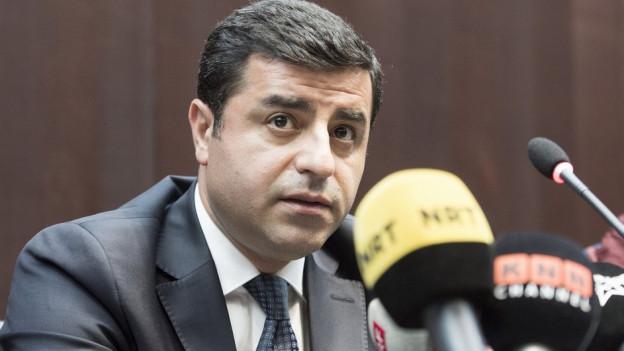 Mann im grauen Anzug an einem Pult, im Vordergrund verschiedene farbige Mikrofone.