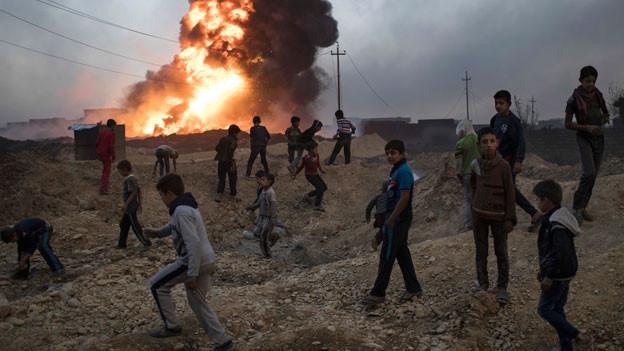 Kinder in der Nähe eines brennenden Ölfelds südlich von Mosul, Irak.