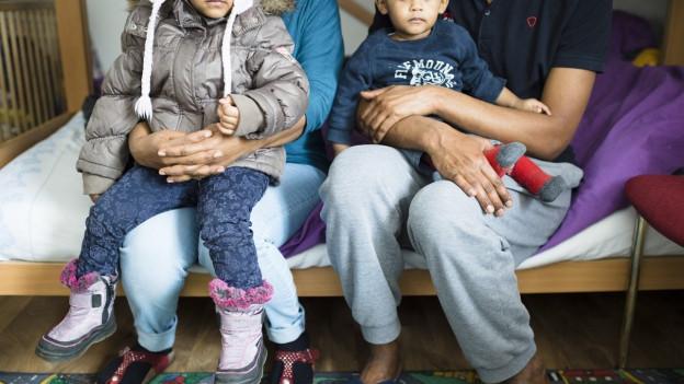 Eine Familie aus Eritrea sitzt auf einem Bett in einem Asylzentrum.