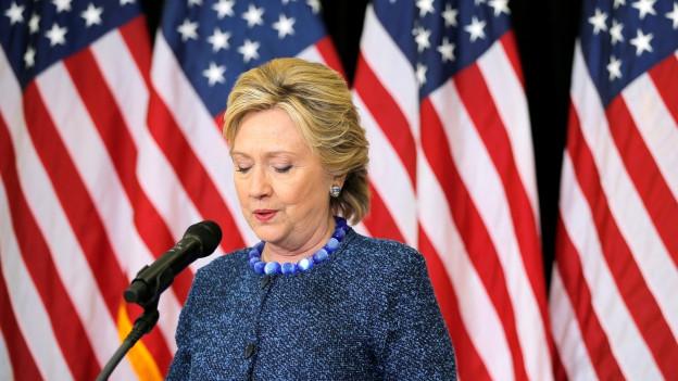 Hillary Clinton an einem Rednerpult, im Hintergrund sind mehrere US-Flaggen zu sehen.