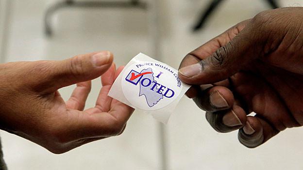 Eine Hand reicht einer anderen einen Sticker auf dem steht «I voted».