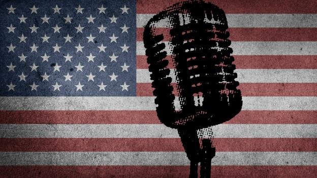 Fotomontage eines Schwarzen Mikrofons auf einer US Flagge.