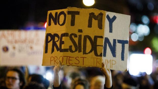 Ein Trump-Gegner hält am Wahlabend in New York sein Schild in die Höhe: Trump sei nicht sein Präsident.