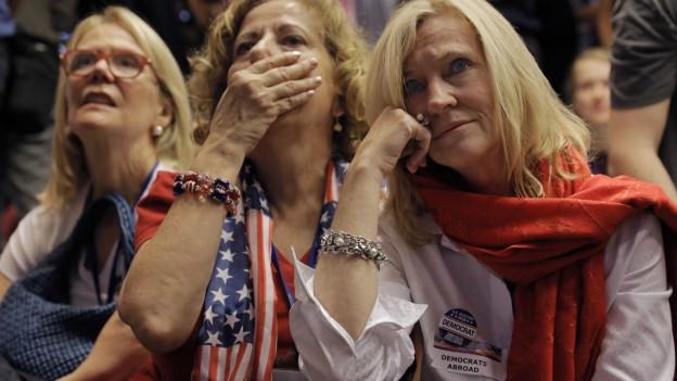 Drei Frauen blicken ungläubig zu, wie Wahlresultate verkündet werden.