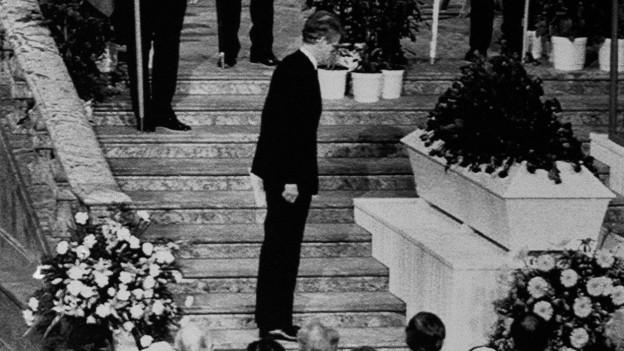 Zu sehen ist eine Beerdigungsszene: Ein Mann, der neue Premierminister Ingvar Carlsson steht vor viel Publikum vor dem Sarg des verstorbenen Olof Palme.