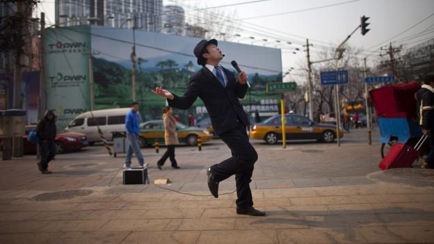 Ein Mann singt mitten in Peking Karaoke und tanzt dabei.