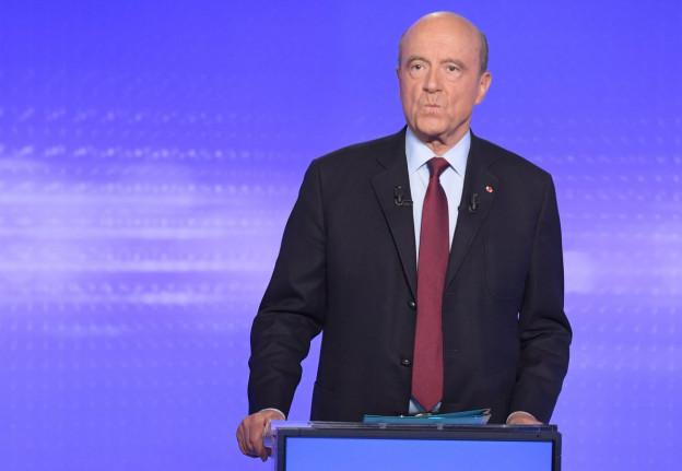 Alain Juppé hinter seinem Podest am letzten Fernsehduell, er blickt zermürbt, Glatze, schwarzer Anzug, blauer Hintergrund (17. November 2016).