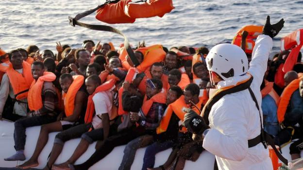 Ein völlig überfülltes Flüchtlingsboot, auf das eine Hilfskraft einen Rettungsring wirft.
