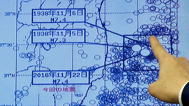 Auf einer Karte zeigt ein Finger auf das Epizentrum des Erdbebens.