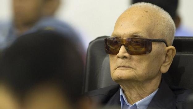 Ein ehemaliger Rote Khmer Anführer sitzt mit dunkler Sonnenbrille im Gerichtssaal.