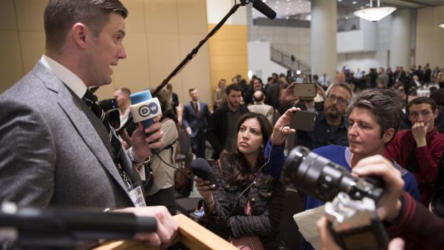 Links im Bild steht Richard Spencer, ein Vertreter der Alt-Right-Bewegung, rechts im Bild sind Journalisten zu sehen.