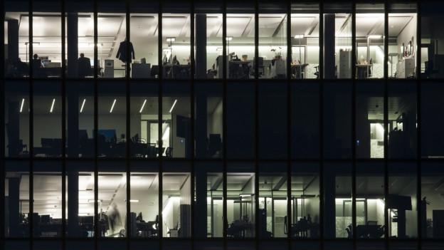 Zu sehen ist die Fassade eines Bürogebäudes, von innen beleuchtet.