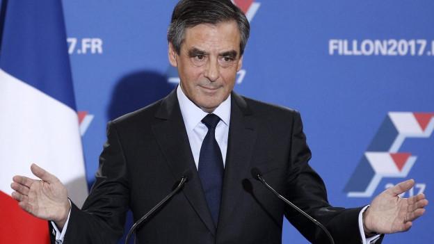 Zu sehen ist François Fillon lächelnd, mit erhobenen Händen vor blauem Hintergrund.