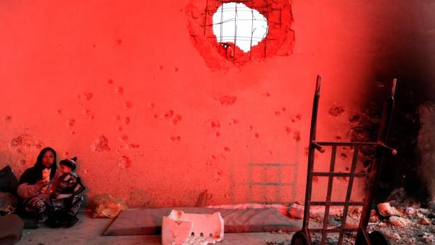 Das Bild zeigt eine Familie in Aleppo, die in einem zerbombten Haus lebt.