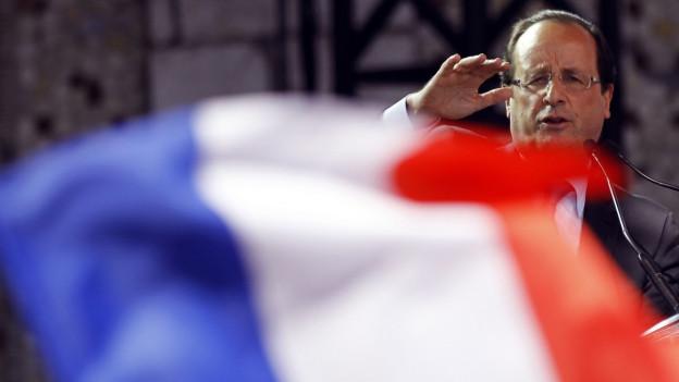 Auf diesem Bild aus dem Jahre 2012 sieht man den damaligen Kandidaten Hollande hinter einer französischen Flagge eine Rede halten.