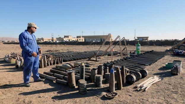 Irakischer Soldat neben Waffen und Munition, die dem IS gehört hat.