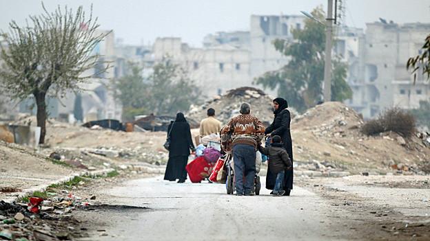 Eine Gruppe Menschen mit Taschen und Koffern auf der Flucht aus Ost-Aleppo.