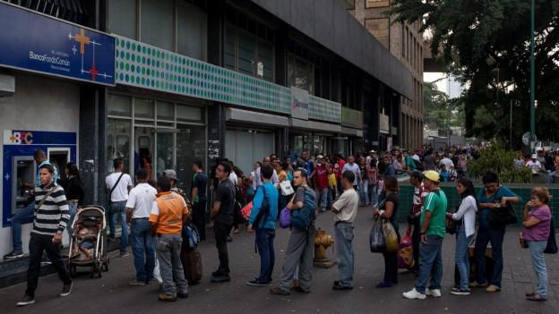 Menschen stehen vor einem Bankautomaten Schlange.