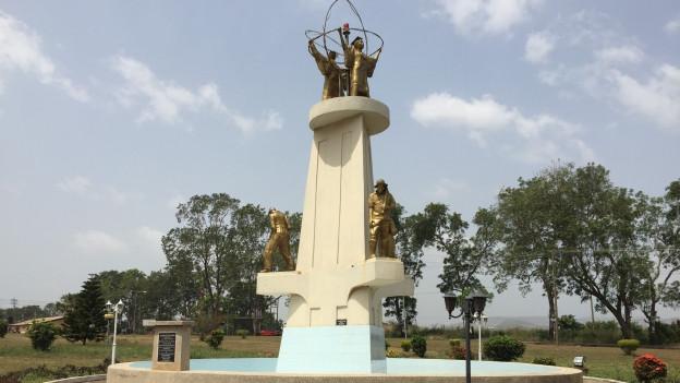 Ein Brunnen mit goldenen Figuren vor Baumbestand