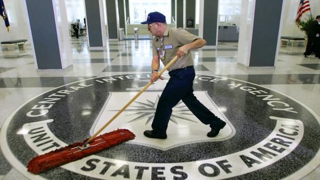 Ein Putzkraft fegt den Boden im CIA-Gebäude.