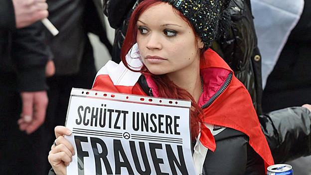 «Schützt unsere Frauen» steht auf dem Plakat, das eine Frau mit rotem Umhang trägt.