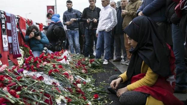Eine junge Frau sitzt am Ort des Anschlags vor Blumen
