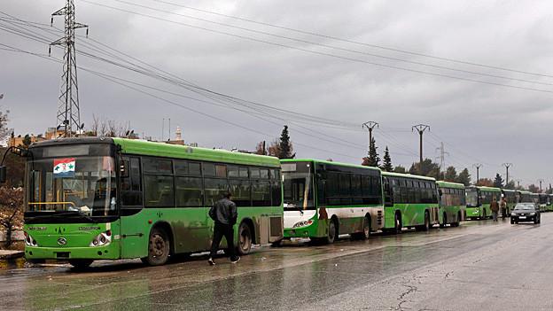 Zahlreiche Busse warten in Aleppo auf den Abtransport Evakuierter.