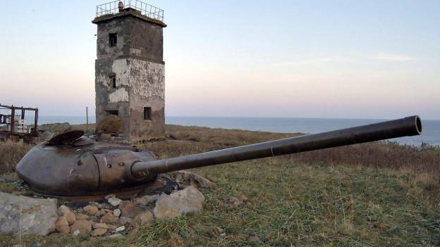 Ein Geschützturm und ein Leuchtturm auf einer Kurilen-Insel.