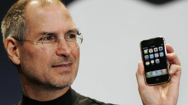 Ein Mann mit Brille hält ein Smartphone in die Höhe.