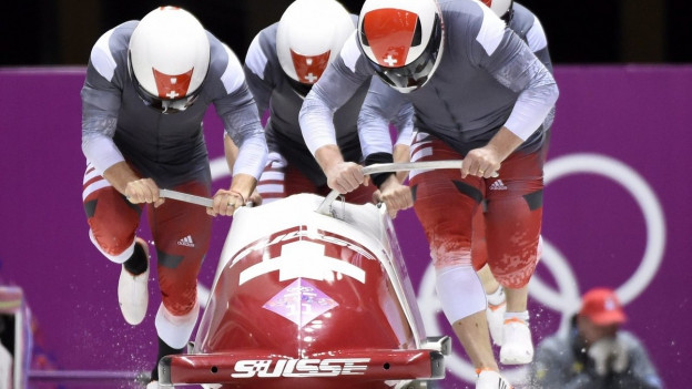 Das Schweizer Bobteam schiebt an den olympischen Winterspielen 2014 in Sotschi gemeinsam den Schlitten an