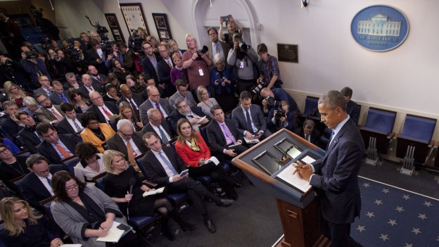 Ein zerknirscht wirkender Obama am Rednerpult von schräg oben, links das Pressekorps sitzende und stehend.
