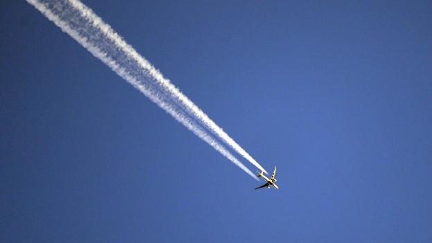 Ein Flugzeug fliegt vor blauem Himmel und hinterlässt einen Kondensstreifen