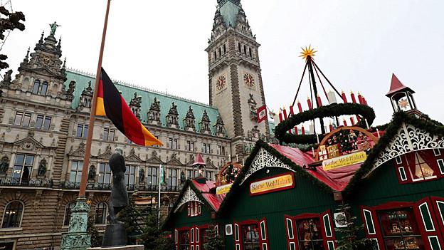 Eine deutsche Flagge vor einem Weihnachtsmarkt auf Halbmast.