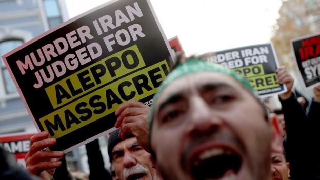 Männer demonstrieren. Im Vordergrund gross der Kopf eines Demonstranten, im Hintergrund ein Banner mit iran-kritischem Slogan.