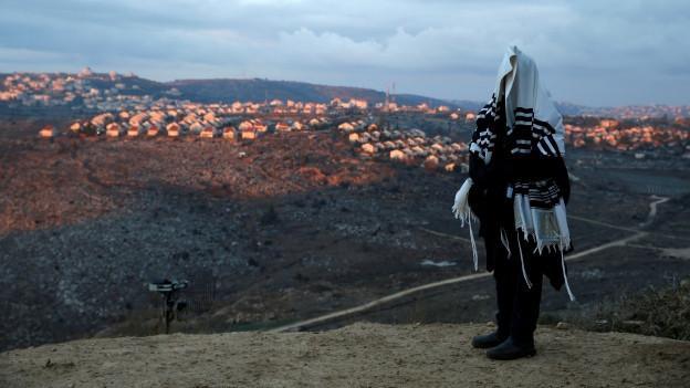 Zu sehen ist ein jüdischer Siedler auf einem Hügel im Westjordanland, dahinter eine umstrittene jüdische Siedlung.