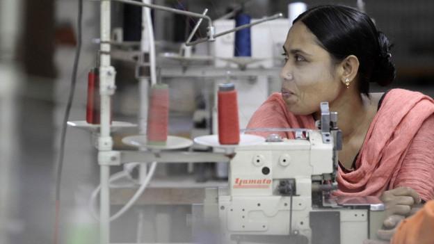 Eine Frau sitzt an einer Nähmaschine.