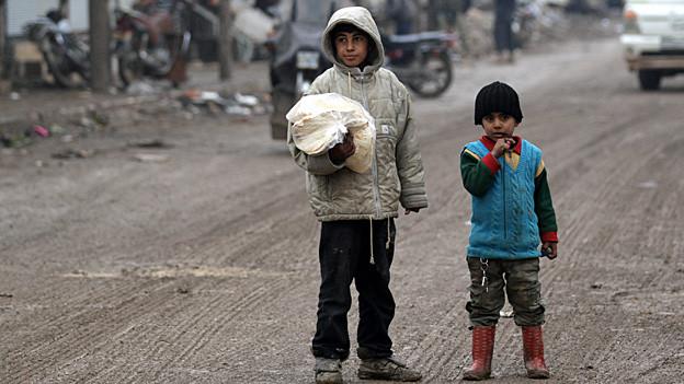 Zwei Buben mit einer Tasche Brot auf einer Strasse im Norden Aleppos.