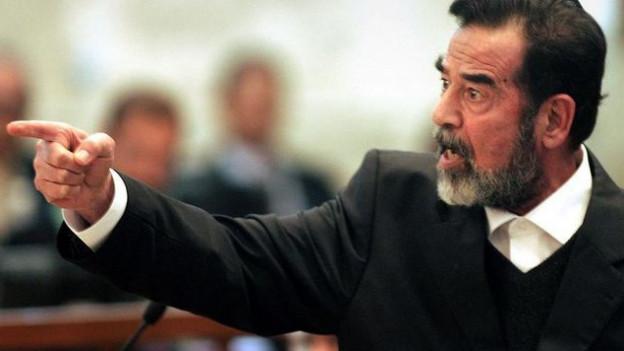 Saddam Hussein mit ausgestrecktem Arm im Gerichtssaal während dem Gerichtsprozess 2006.