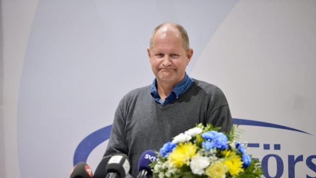 Mann mit Blumen lächelt verlegen.