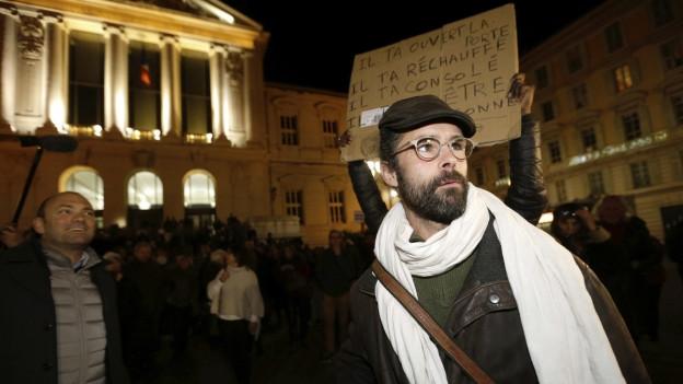 Cédric Herrou ist zu sehen, wie er vor einer Gruppe von Unterstützern steht.