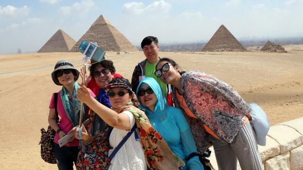 Touristen machen vor den Pyramiden von Gizeh ein Selfie mit dem Smartphone.