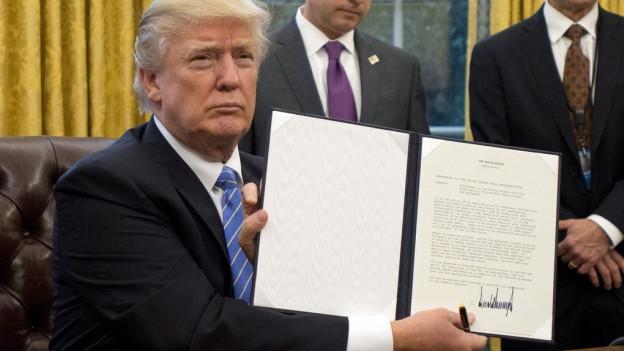 Trump hält seinen Erlass in die Kamera.