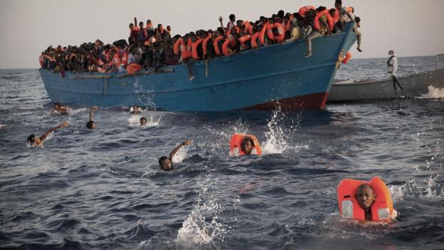 Ein überfülltes Boot mit Flüchtlingen, ein paar von den Flüchtlingen sind im Wasser.