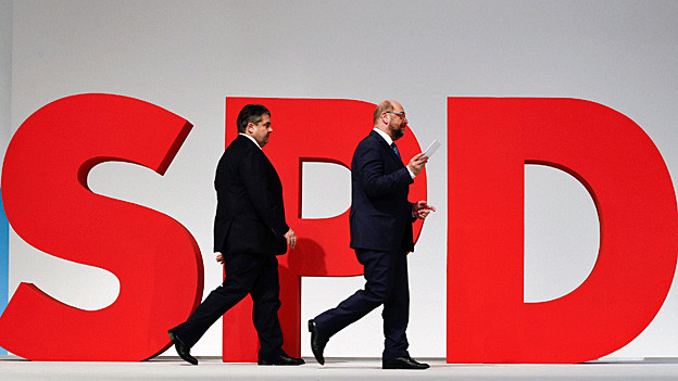 Sigmar Gabriel und Martin Schulz gehen vor den mannshohen, roten Buchstaben SPD vorbei.