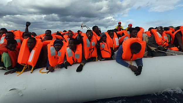 Ein Boot voller Flüchtlinge in roten Rettungswesten.