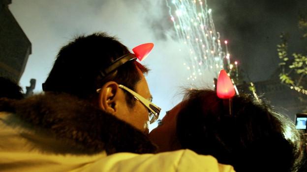 Besucher küssen sich während dem Feuerwerk zum Beginn des neuen Jahres