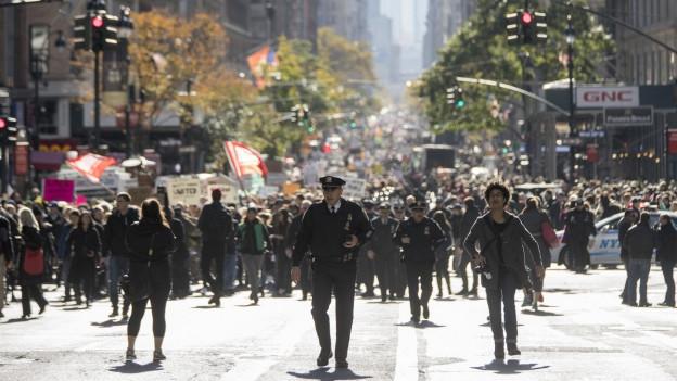 Protestierende Menschenmenge in einer breiten Strasse in New York, sie schwenken Fahnen. In der Mitte ist ein Polizist zu sehen.