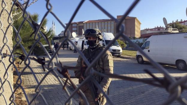 Maschendraht, Polizist, dahinter Gerichtsgebäude