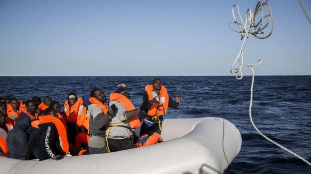 Migranten in einem Schlauchboot auf dem Mittelmeer.